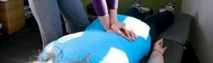 Alison mobilizes the patient's spine