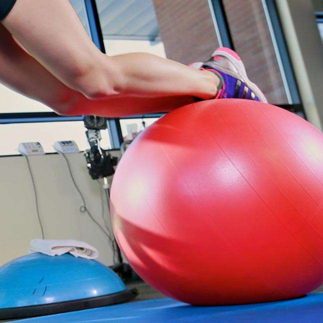 Closeup of youthful female runner doing pikeups on the physioball