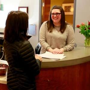 A therapy client stands in front of a smiling receptionist to schedule an appointment
