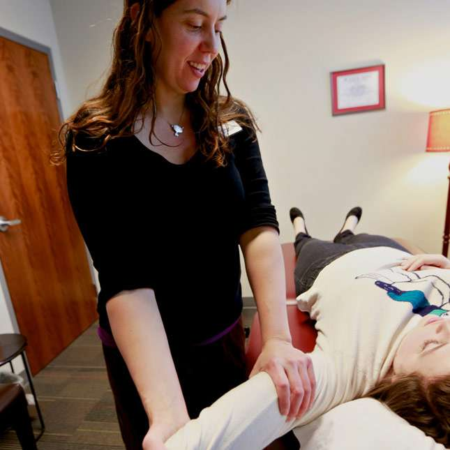 Kari Szukalski smiling while stretching the arm and shoulder of a patient