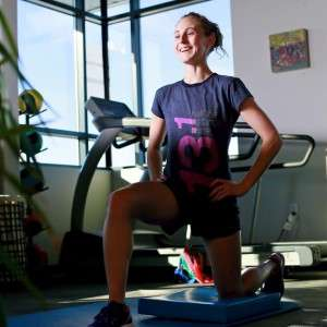 Smiling athlete in gym setting does lunges for rehabilitation