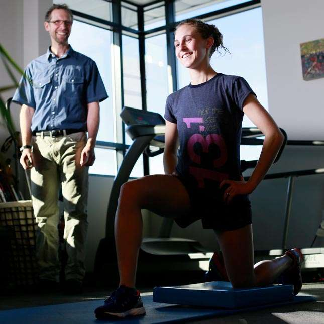 Physical Therapist observes his patient doing lunges during rehab