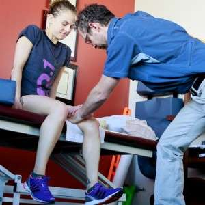 Patient sits on therapy table while male therapist does manual therapy on her knee