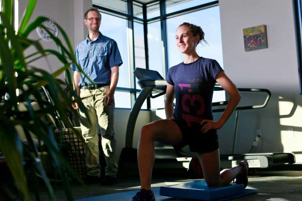 Young female runner does a lunge with therapist ready to help